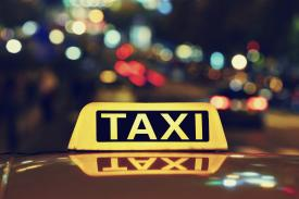Photo of a taxi sign at night
